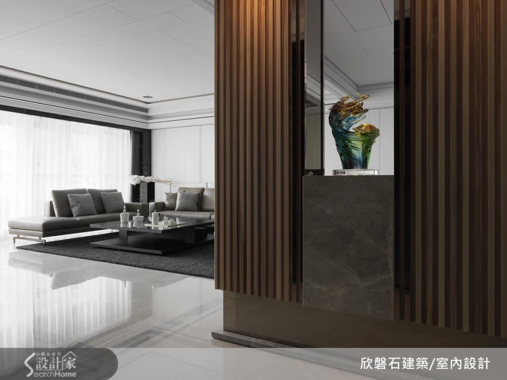 玄關處的木格柵門片和大理石交錯設計,彰顯大器感,底部的明鏡設計則營造出輕盈漂浮感。