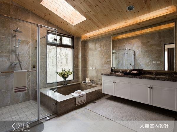 在家也能感受泡湯放鬆之樂!設計師運用自然建材的木石,創造出氣派感十足的衛浴空間,上頭斜屋頂的造型,更納入了自然採光的設計,讓人有泡湯屋的愜意放鬆之感。
