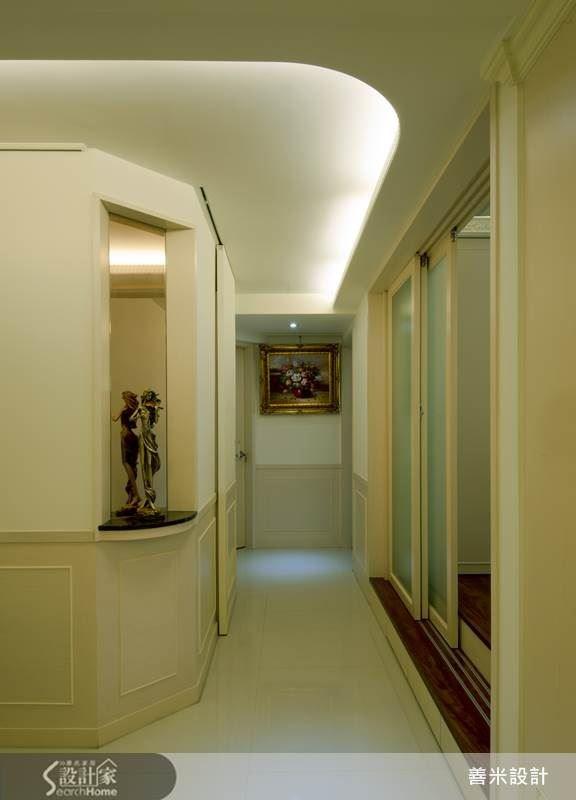廊道天花板以圓弧收邊並搭配間接燈光,結合轉角端景與廊道底端的掛畫,讓動線柔和且分明。