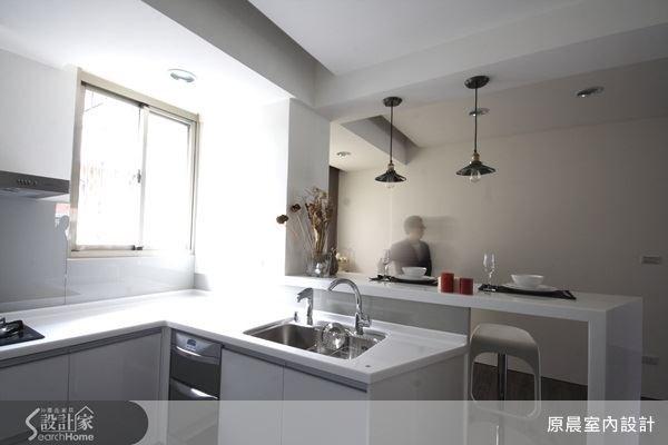 以白色系為主色調的簡約廚房,低矮的吧台則是餐廳和休閒空間的區域界定。