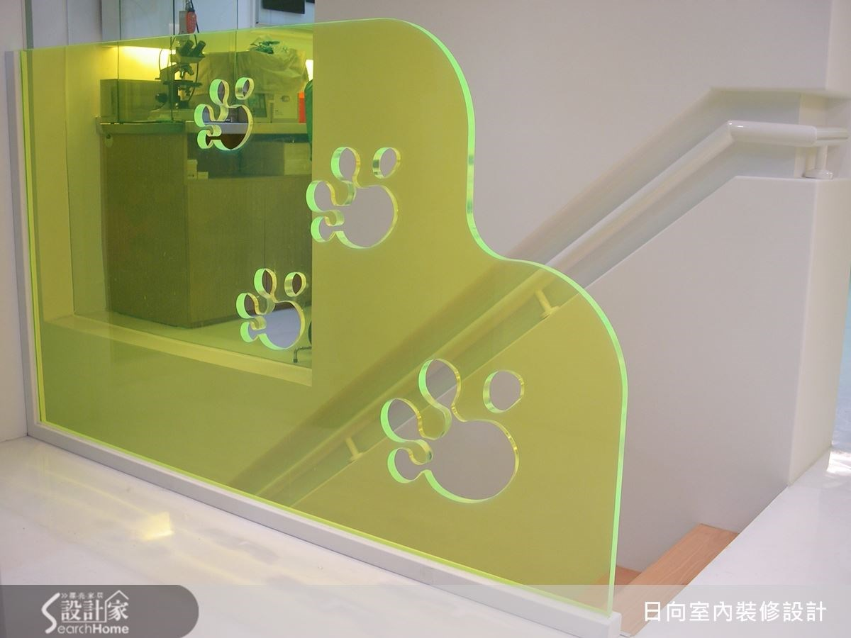 利用壓克力板作為樓梯的分隔之用,狗腳印的挖洞造型,讓牆面多了點玩心設計,白色壁面也展現出空間的潔淨感。