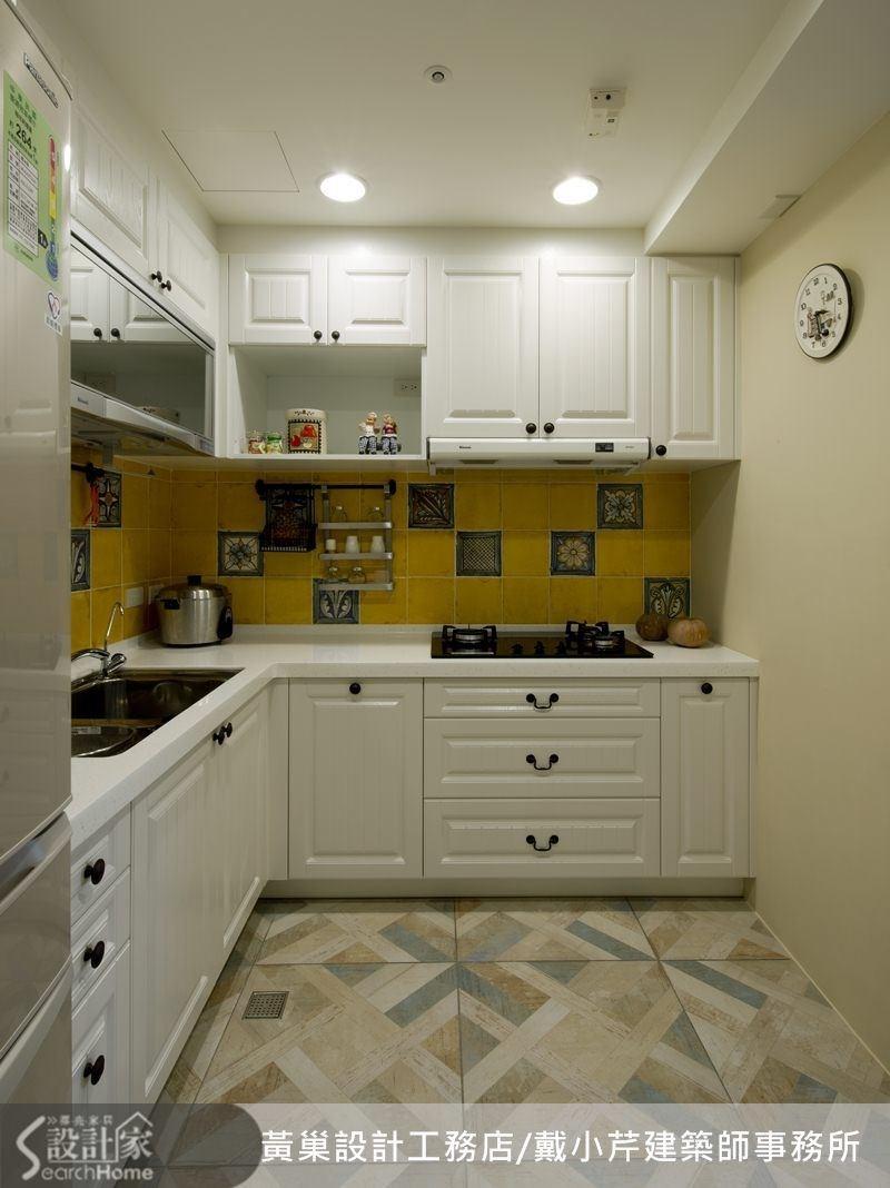 L 型廚房配備白色的鄉村風櫥櫃,中間是芥末色亮面瓷磚+彩繪磁磚,整齊有致。