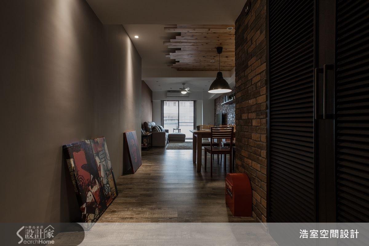 走進玄關,就能看到以仿舊木頭材質的鞋櫃,呼應著以磚紅色為主體磚牆的設計,搭配具有現代感的畫作隨性置放於地上,增添了空間的時髦與設計感。後方的客餐廳空間一覽無遺,讓原本狹長的空間顯得寬廣深邃。