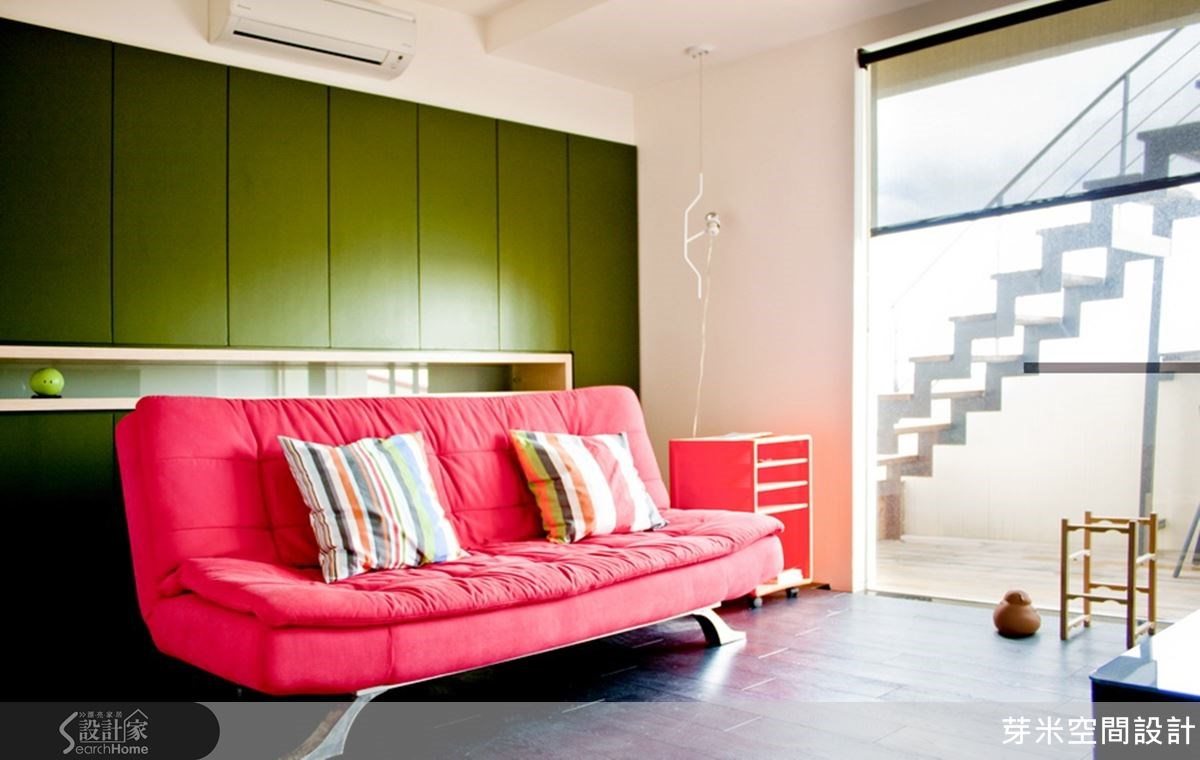 沉穩的深綠收納櫃配上輕快的紅色沙發,特殊的配色,以及一軟一硬材質造成衝突之美,提升空間的品味及質感。