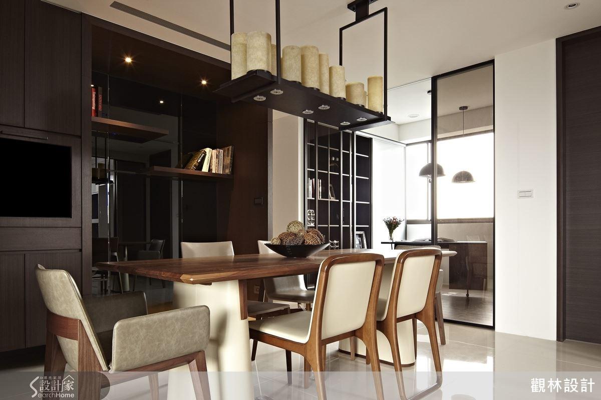 長型的吊燈與木質餐桌營造出溫馨感,後頭的空間(黑鏡前方的空間)也預留給未來擺放鋼琴使用,搭配間接燈光,別有一番風情。
