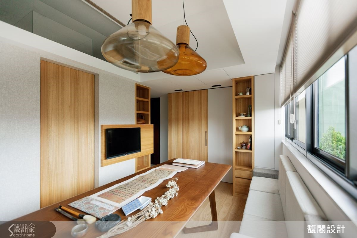 客廳區保留最大挑高,以白色為基調,搭配溫潤的木質調設計,呼應屋主喜歡書法、禪坐的自在生活型態。