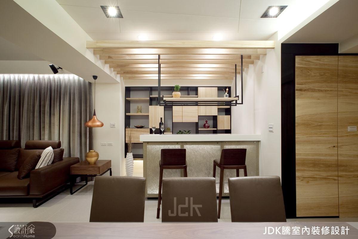吧檯後配置整面收納牆櫃,用梧桐木皮與黑色框架凸顯視覺效果,並將收納空間採不規則大小的格狀切分,成為一幅具備收納機能的藝術牆面;同時,天花板也配置木格柵與間接燈光,營造具氣氛的光影效果。
