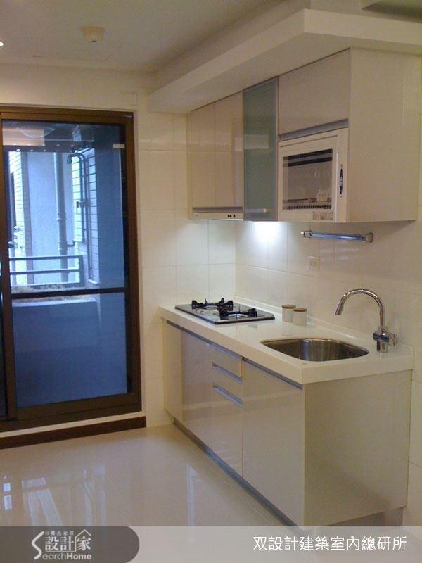 廚房區域以清玻璃門區隔陽台空間,讓陽台的採光得以進駐,而潔白的廚房流理台則給人清爽美好的印象。
