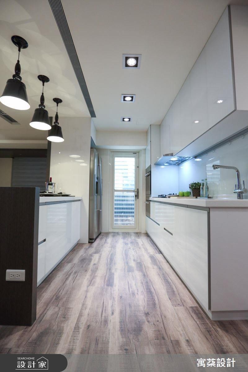 吧台是料理工作台,也是跟客廳的連結,也可當中島使用;並採人造石打造吧台,餐櫥櫃則以白烤玻璃為材質,再點綴三盞黑色的燈飾,維持整體的黑白色彩基調。
