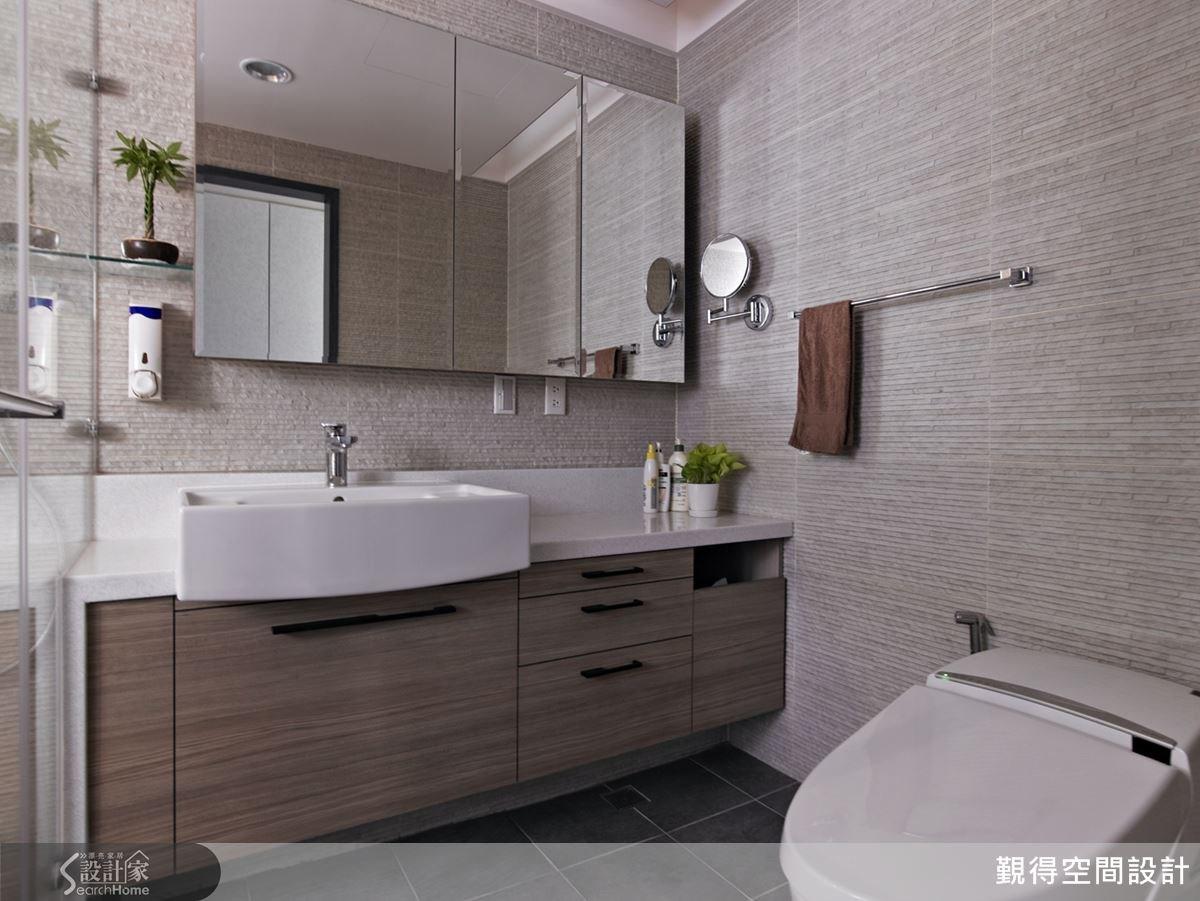 衛浴空間以清玻璃隔門創造乾濕分離設計,讓空間感更通透寬敞;洗手台搭配鏡櫃,帶來豐富的收納效益。