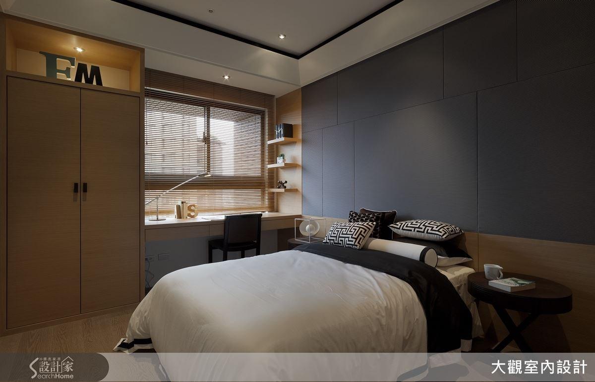 以深灰色打造床頭主牆,營造沉穩又時尚的空間氛圍。櫃體上方的專屬英文縮寫則展現了獨特巧思。
