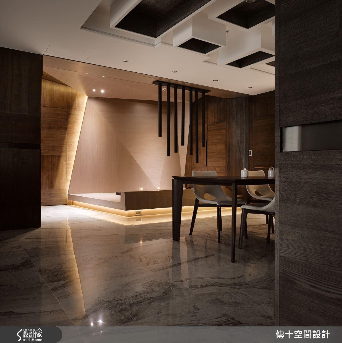 入口其一軸線為玄關、餐廳、多功能室。餐廳天花板做出盒狀燈光設計,形成獨一無二的吸睛焦點;後方多功能室則加入折板幾何元素,但同時以溫潤木皮注入禪風氣息,搭配獨家的懸吊訂製燈具,形成療癒氛圍。