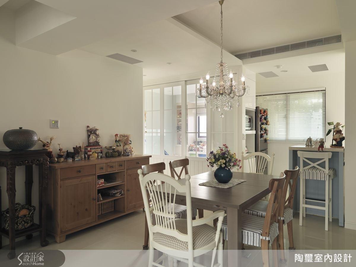 餐桌上方安排一盞水晶主燈,讓美感更加提升;後方的木質餐櫃則兼具收納與端景的作用。