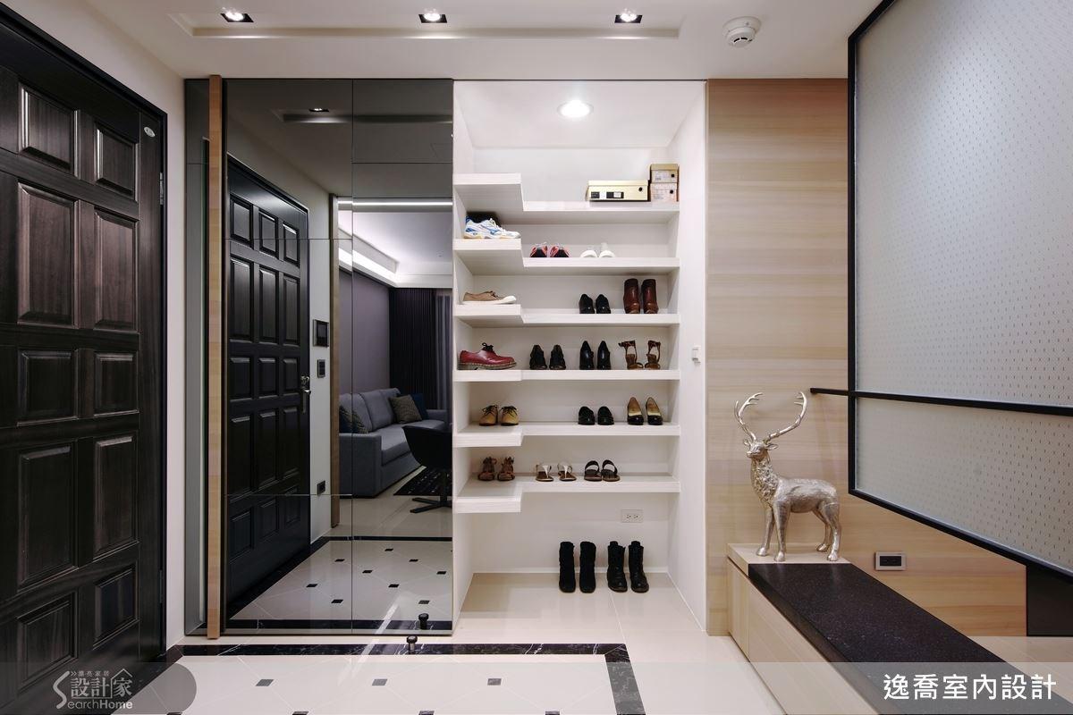 玄關的鞋櫃結合了灰鏡的材質,並且以幾何切割方式呈現,裡片的 L 型的層板架則一一收納好鞋子。