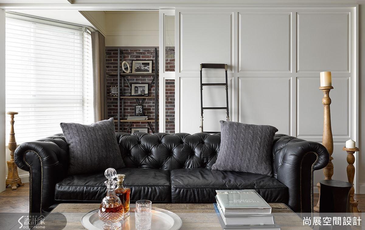 玄關以屋主的收藏與相框做擺飾,而客廳沙發則選擇穩重色系作為空間重心。