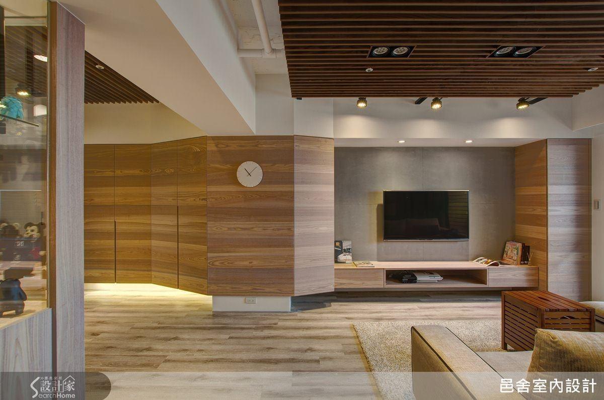 電視牆旁是原有的主要結構柱體,與玄關之前正好形成明顯的畸零空間,邑舍團隊以木皮順著柱體的角度包覆,以弧度造型延伸整個電視牆面,搭配仿清水模牆面,化缺點成特色。