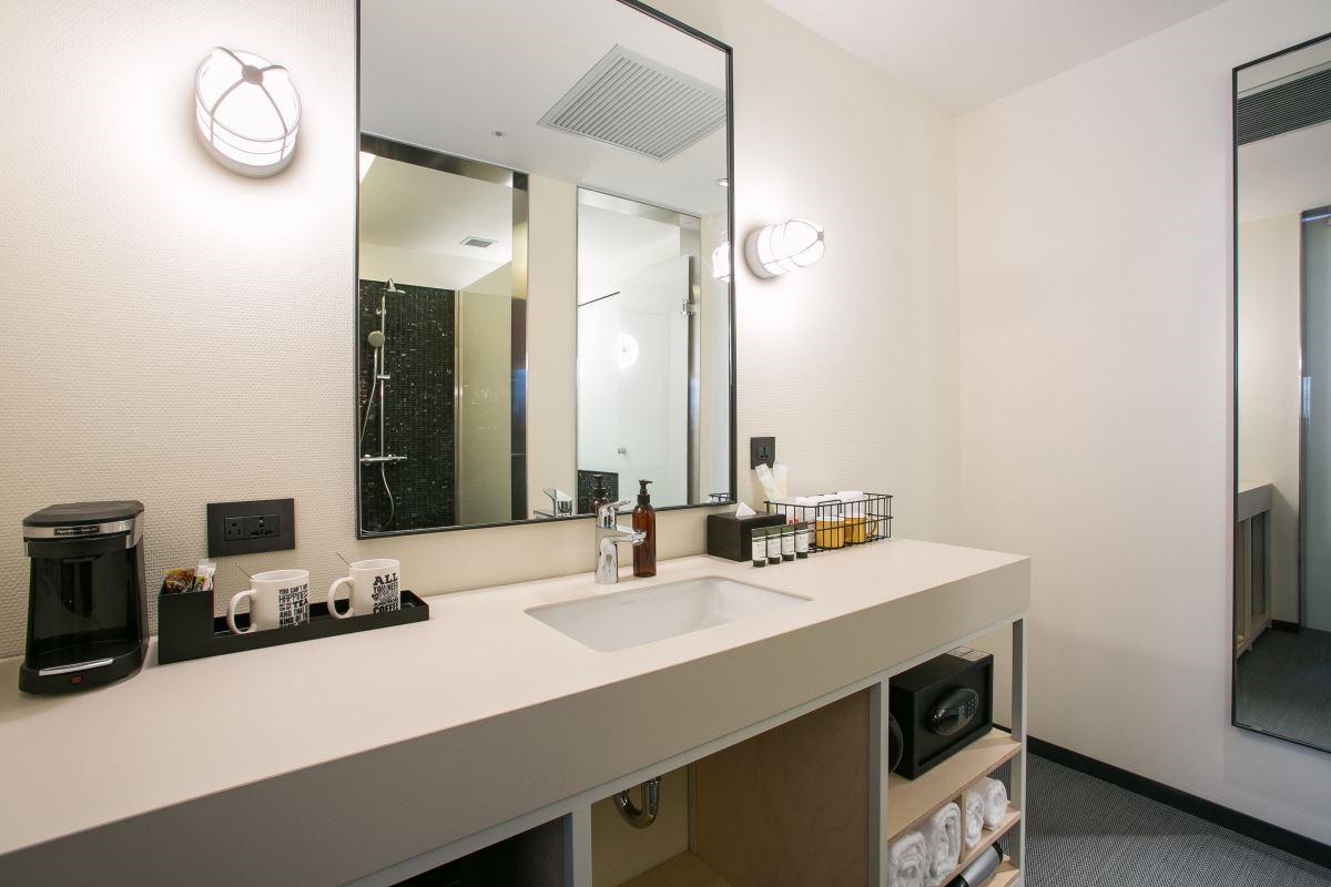而衛浴的設計則以簡單的乾溼分離,並加上黑色馬賽克磚,表現時尚氛圍。圖片提供_台北中山意舍酒店 | amba Taipei Zhongshan