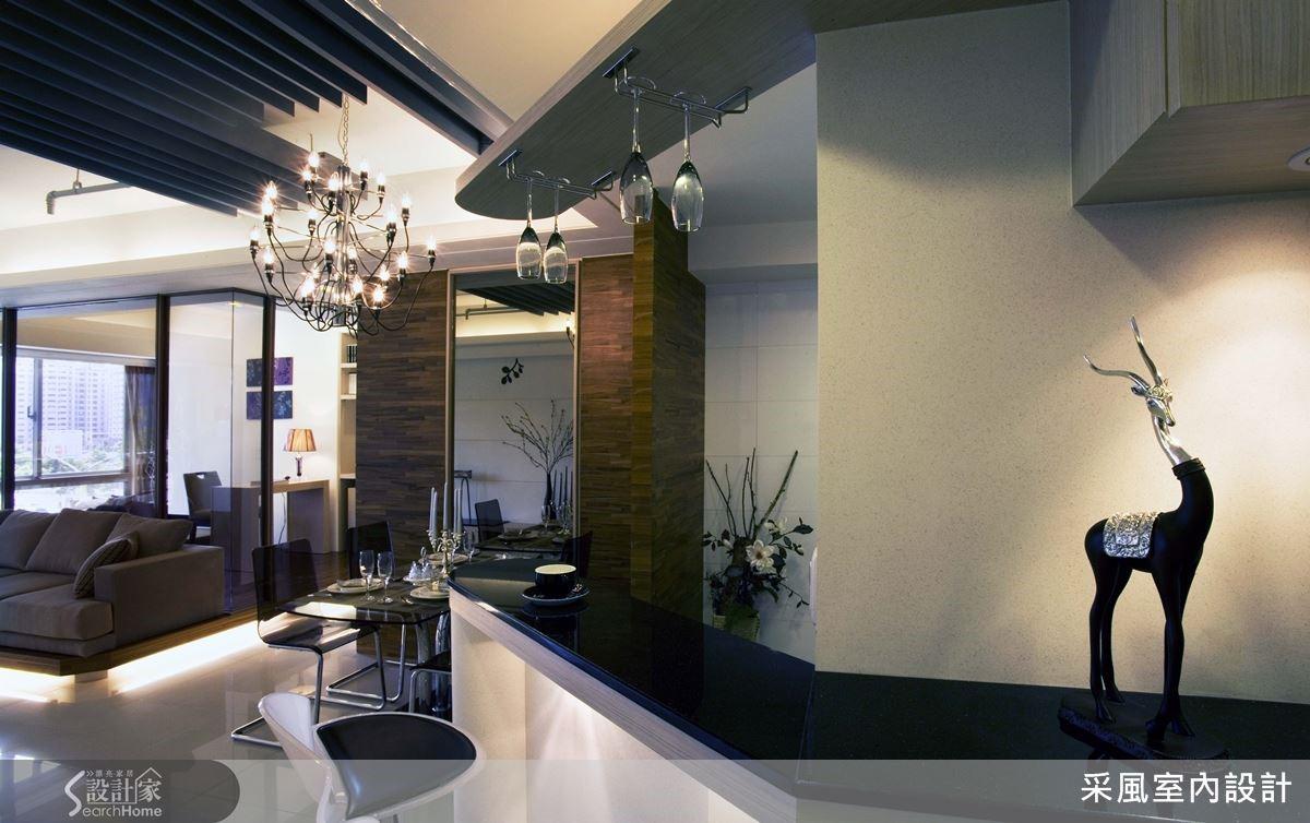 一進門便可見到由餐廳延伸過來的環繞吧檯,黑金鋒大理石檯面化身玄關端景桌,擺放屋主喜愛的藝術品,配搭一旁餐廳懸掛的造型吊燈,組構出亮眼迎賓氣勢。