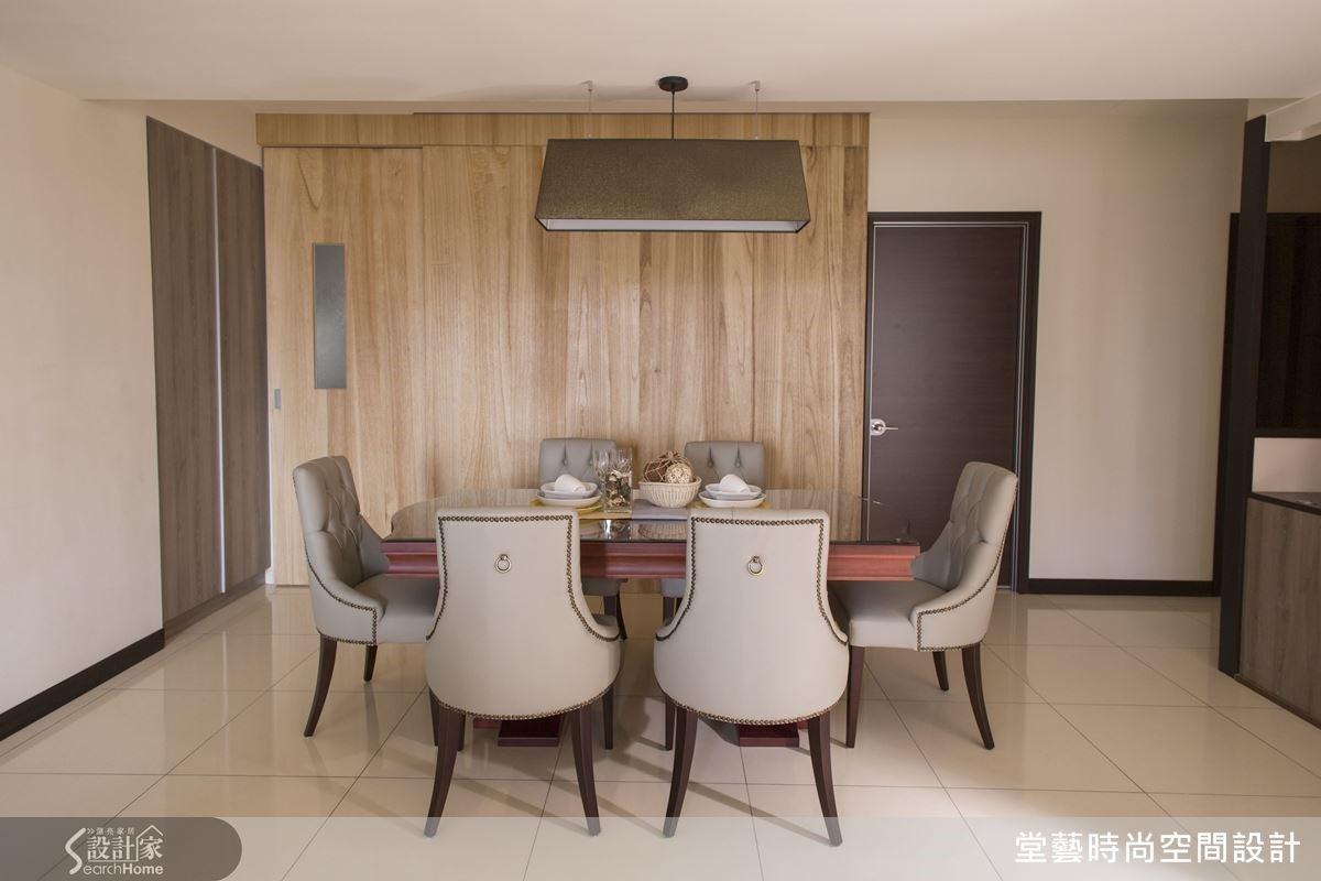 餐廳主牆以鋼刷梧桐木打造出輕鬆愉悅的用餐環境,廚房木質拉門設計解決做菜時油煙四處飄散的問題。