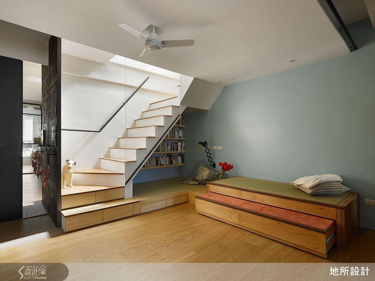 客廳以臥榻型態打造而成,與樓梯下的閱讀空間結合,使用彈性變得更豐富,臥榻下還可再拉出一層以軟墊鋪設的臥榻,形成孩子的遊樂區。