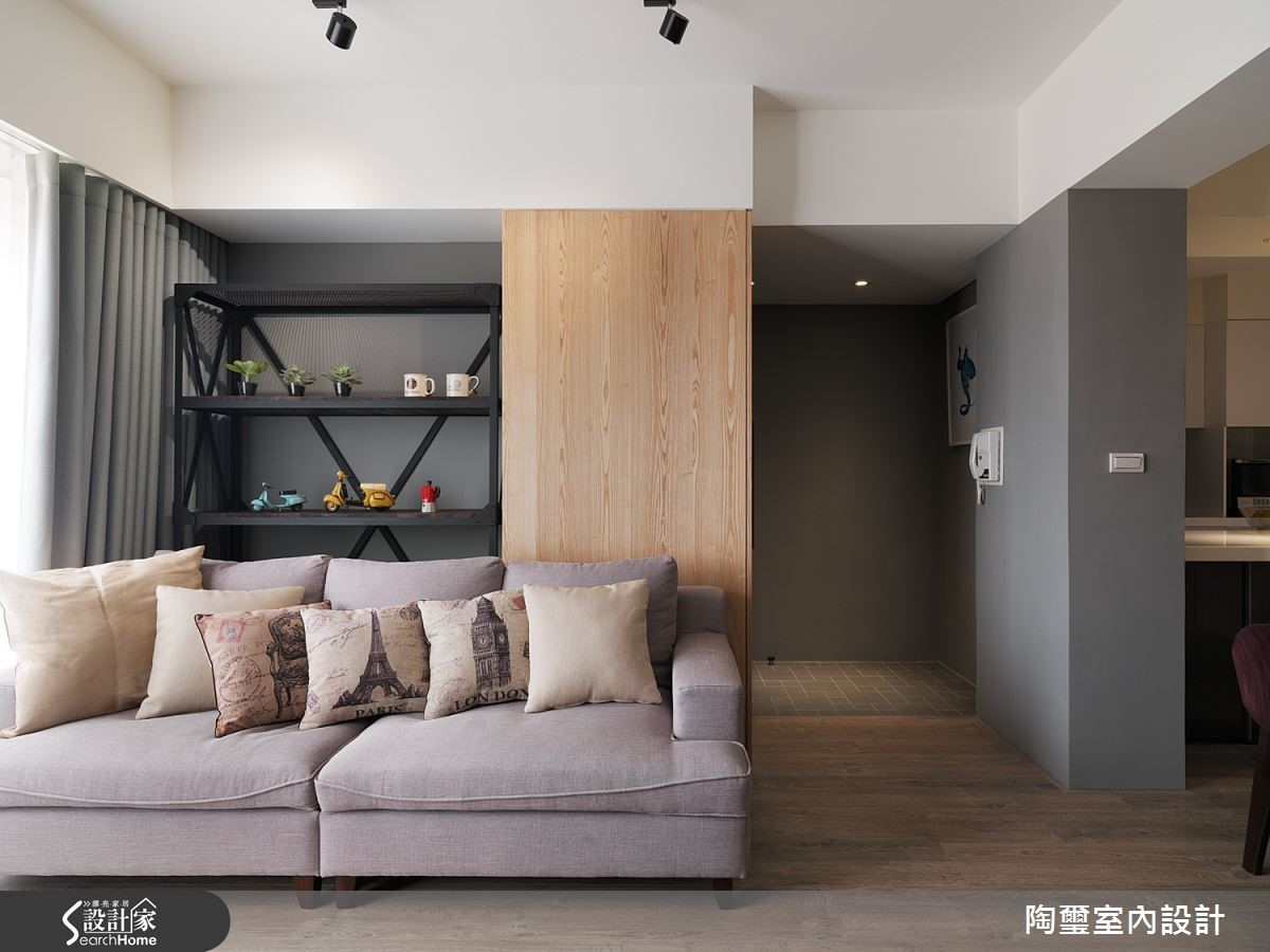 沙發後方的木材質元素乍看之下只是牆面,但其實隱藏了推拉式的鞋櫃,讓收納機能與美感合而為一。