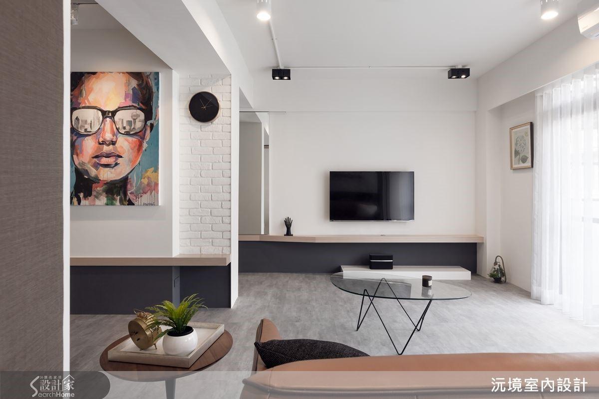 客廳電視主牆與餐廳的展示壁面,兩個平行、不相連的量體,藉由同樣高度的橡木軸線、達到視覺延伸、空間連結效果。左側立柱表面鋪貼文化石減輕量體壓迫感,同時裝飾黑色掛鐘、一旁的畫轉移焦點,柱體就此融入設計當中、成為餐廳牆面的延伸。畫作主題為繽紛女性臉龐、眼鏡反射出城市影像,成為女主人穿梭世界各地的誠實寫照。