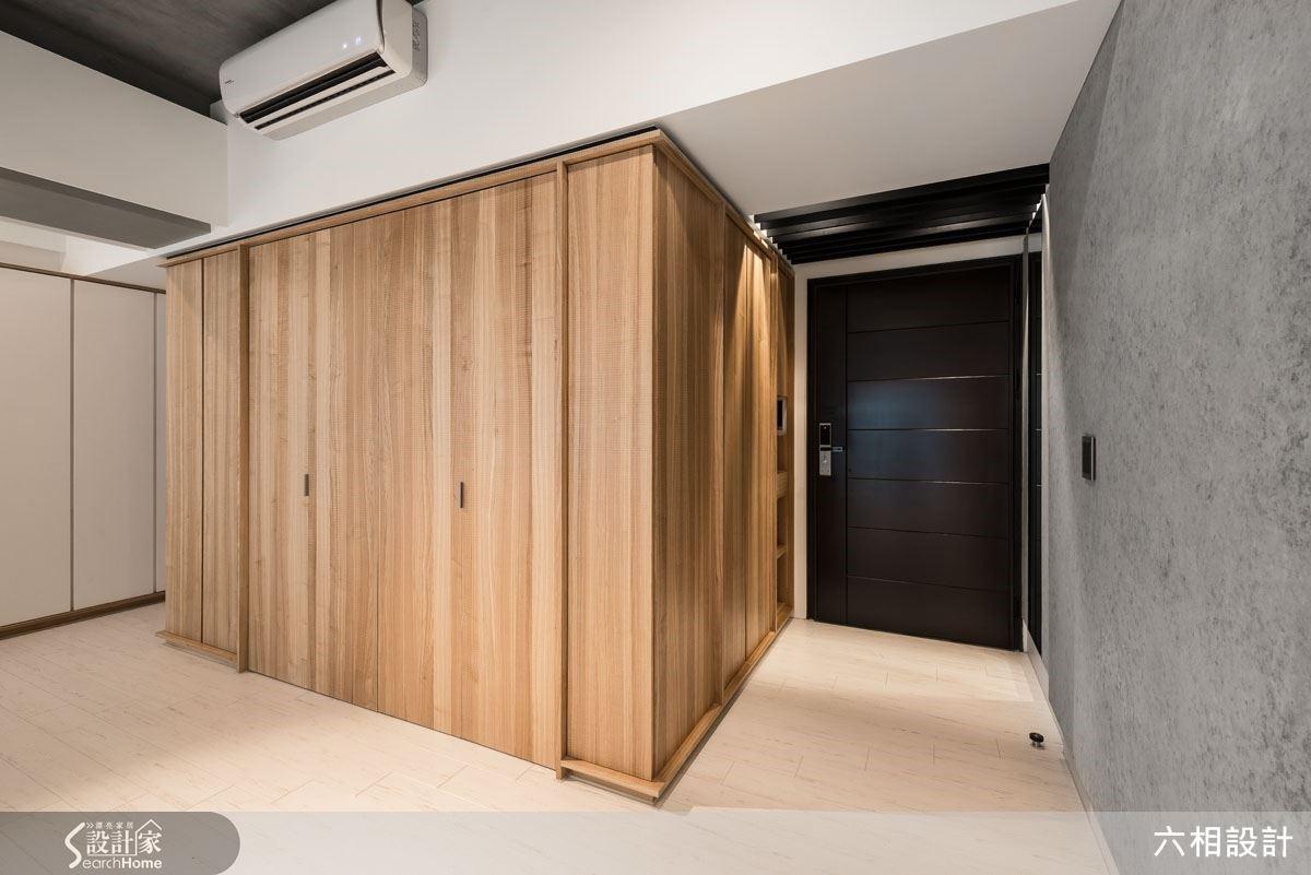 入口旁原本是樓梯位置所形成的凸出角落,並形成不少畸零空間,設計師將整個角落圍塑成一座木質感的大型量體,同時利用畸零角落賦予玄關鞋櫃與小型收納室的功能,創造機能的同時也讓整體視覺效果更俐落清爽。