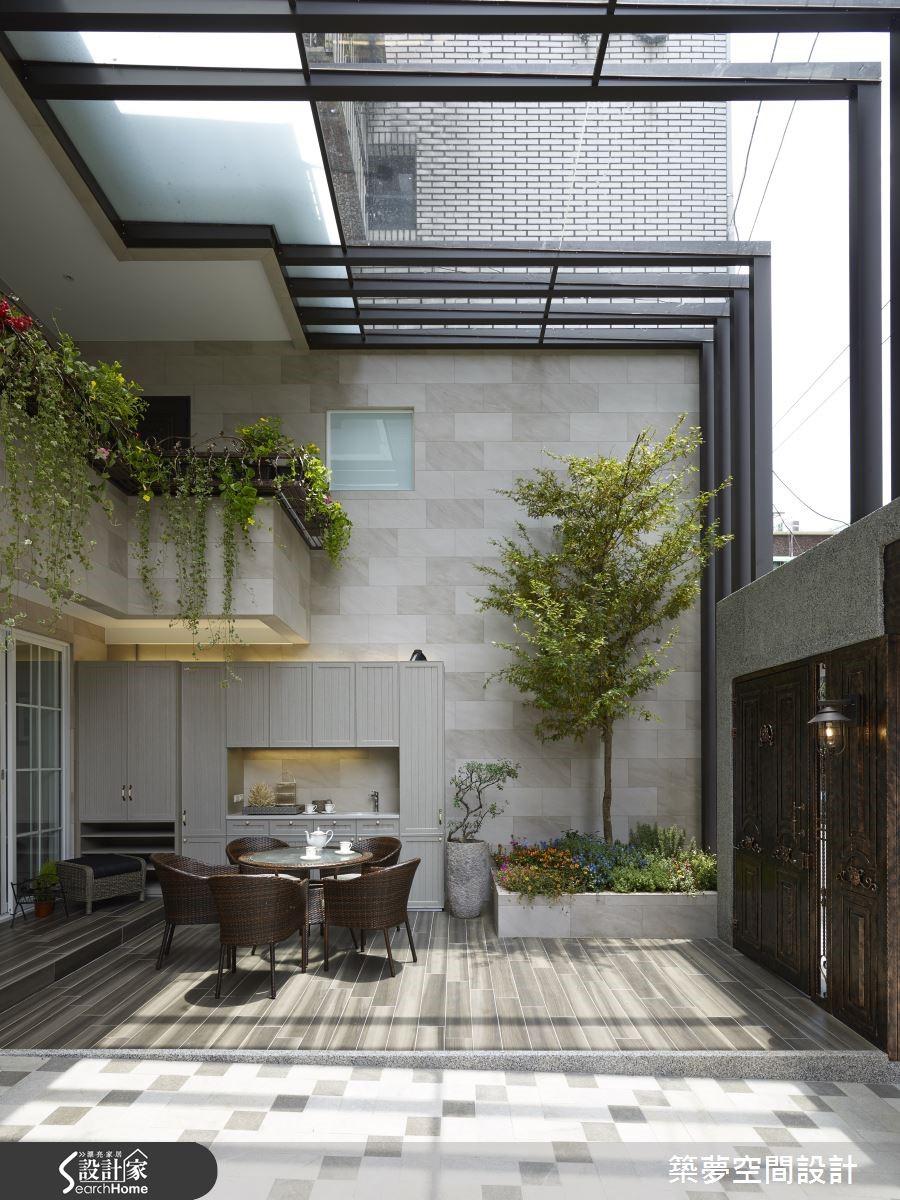 車庫、走道共享庭院空間,墊高木紋磚帶出自然氛圍,砌出英式庭園,吧檯、大衣鞋履一氣收整於防水木櫃中。高尺度的遮罩精算角度,即使下雨天也能戶外午茶。