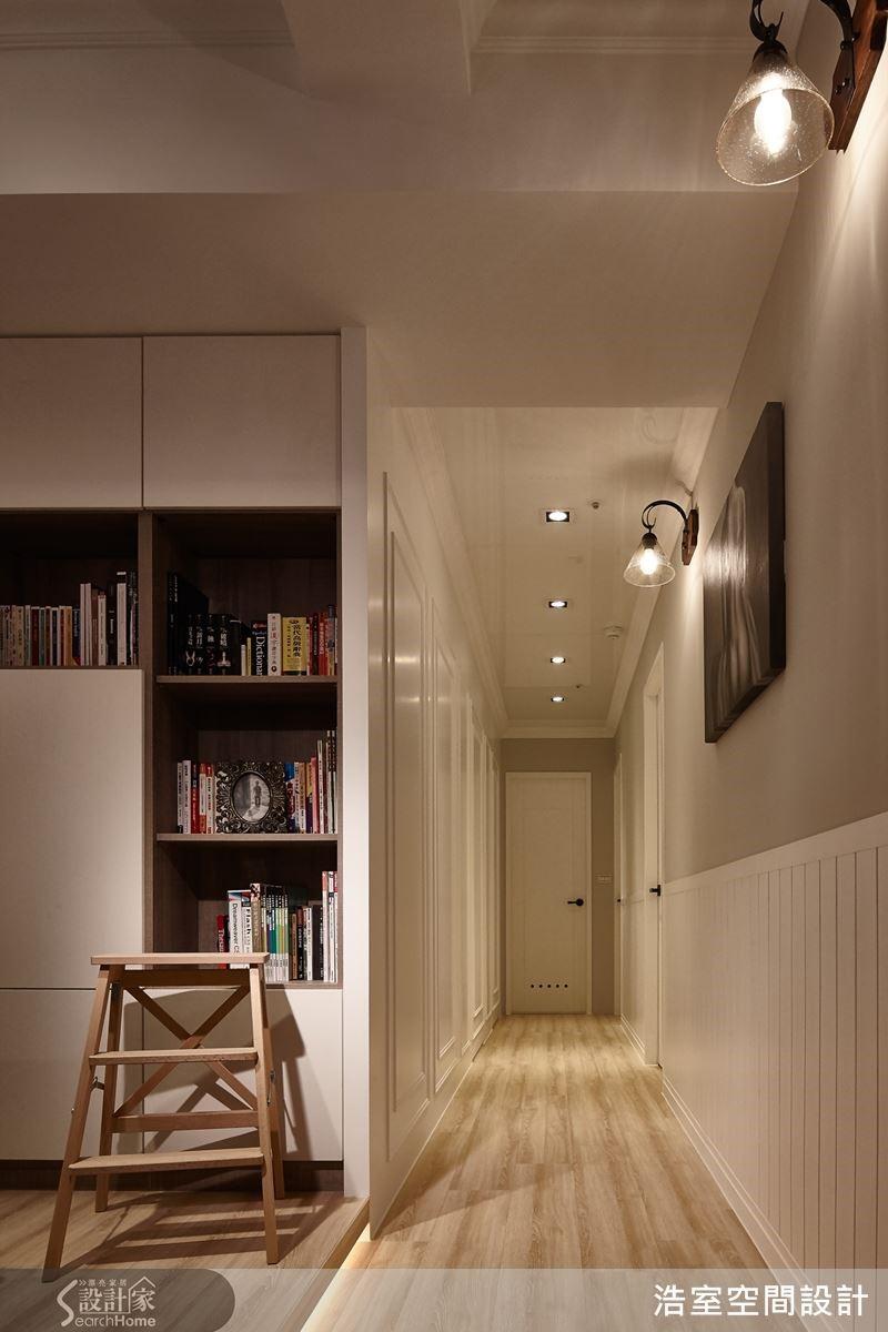 走廊左側牆面以線板修飾並隱藏臥室門,右側牆則以壁燈打亮層次感,讓走廊不會顯得狹隘。
