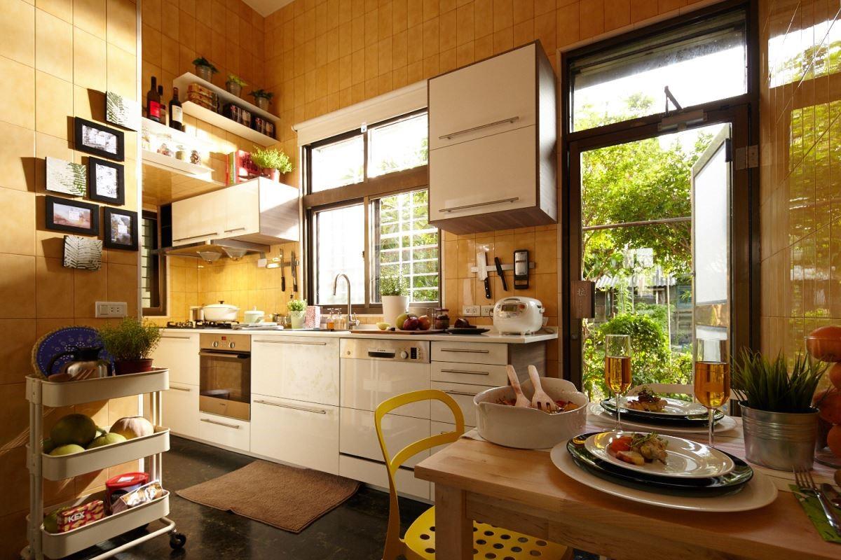 選擇木色系的櫥櫃去做延伸,搭配窗景,讓居住者可邊下廚邊欣賞後花園綠意,創造愜意生活。 攝影_黃暉中