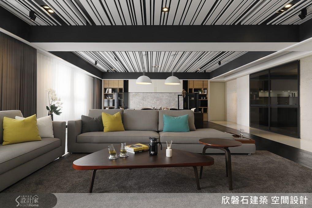 以灰、黑(暗藍)、白構成的靜素空間,由於天花板的深藍線條與沙發上幾顆抱枕的跳色而顯出精神。