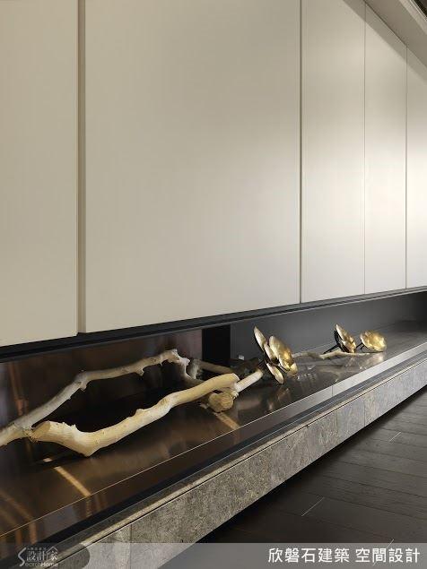 長列的白色吊櫃底下,以深色鈦金板及灰褐色的安格拉大理石構成展示凹槽。