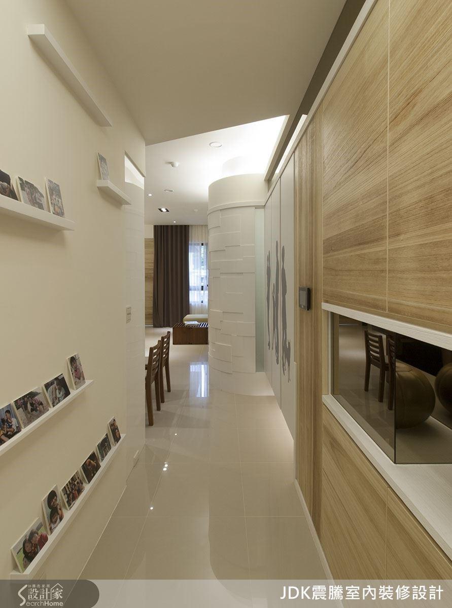 玄關是踏進一個家的開始,也正是屋主一家表露情感的始端,設計師不僅客製化了一面專屬於照片的展示牆,還特別選用梧桐木的暖色調與自然的氛圍,細細的反映出兩者的關聯性。