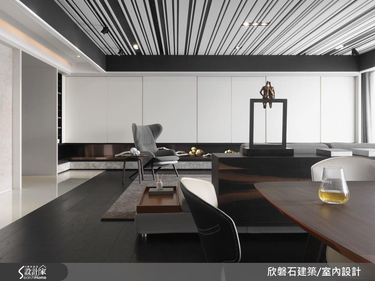 這空間大量運用接近墨黑的深色,同時也以高比例的淺白色系來中和。電視牆這道立面幾乎全為純白色吊櫃,圖左的隔間牆則貼覆米色大理石。清淡可人的淺色立面,消弭了大量暗色可能引發的沉重、冷漠之感。