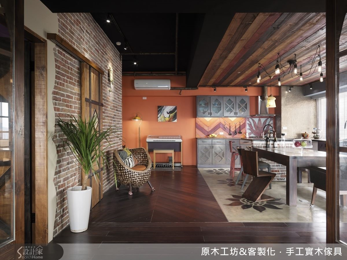 V型拼接地板,與紅橘牆面、幾何廚櫃相對應,將空間做出區分,設計師善用材質、形狀、色彩的組合,不須隔間則輕易創造出空間的區隔。