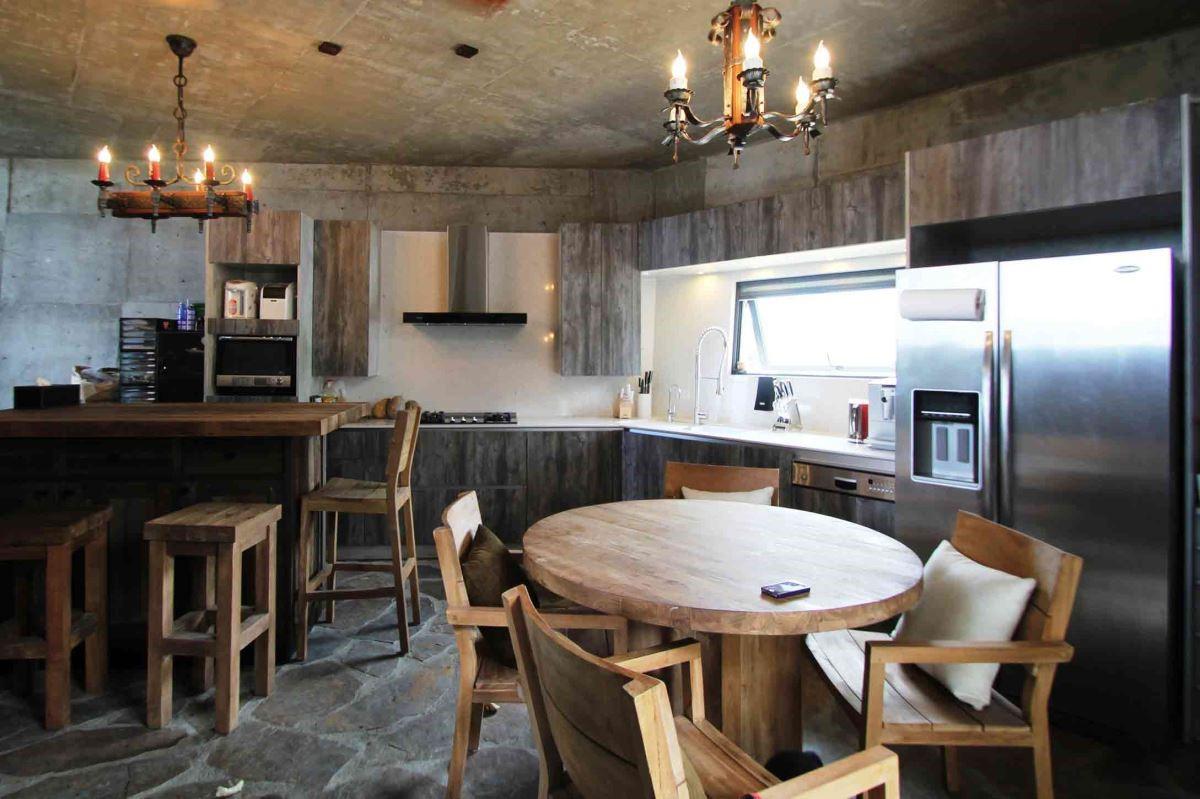 利用石材地面、石紋廚具及厚切面的木質餐桌與吧檯,突現工業風呈現原始材質風貌的精神。