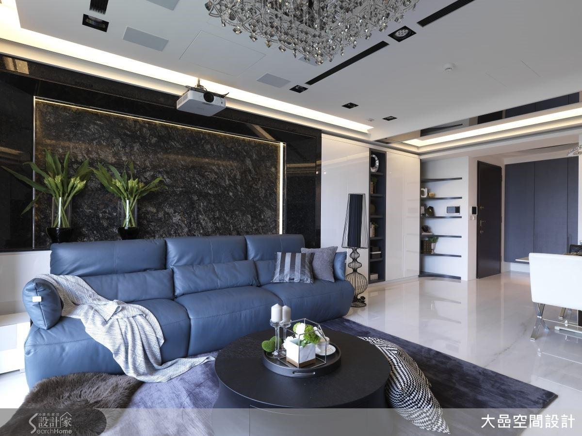 洗鍊沉穩的灰色沙發,從容地坐落在深黑結晶大理石背牆前,堆疊客廳層次感,框線語彙與天花間接照明互相對應。