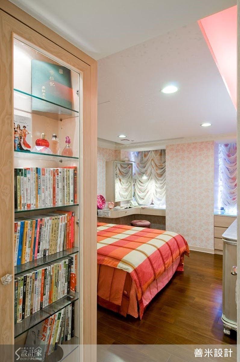 女孩房利用一進門的過度空間設計一座書櫃兼展示櫃,修飾單調的白牆設計。化妝檯旁有一根柱 ,設計師透過 L 型的化妝檯面設計與化妝鏡巧妙消弭視覺上的突兀感。