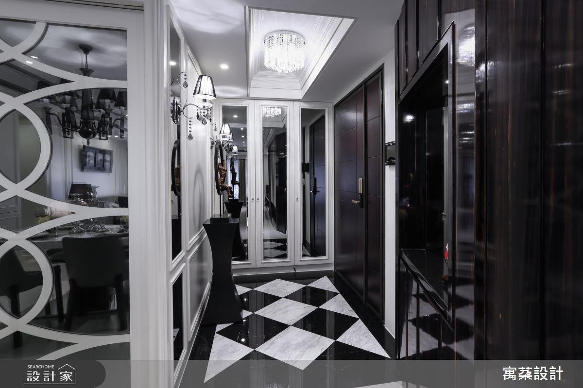 玄關是豪宅的接見廳,地坪以簡約的石材拼花,對應立面長型灰鏡,映射線板堆疊的天花中的水晶吊燈,讓整體設計交相輝映。