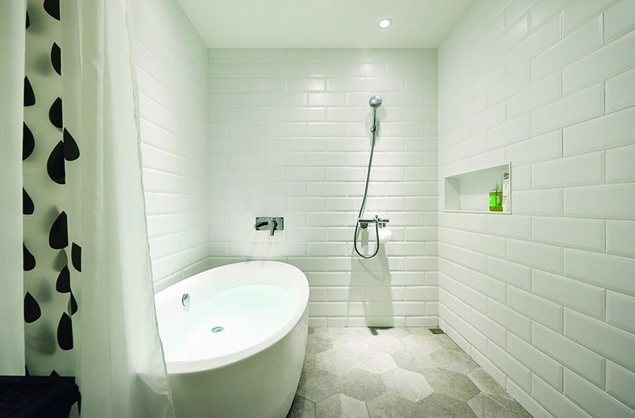 有別於淋浴門的設置,主臥衛浴採用浴簾方式區隔乾濕區,空間少了門的界定才更能感到寬敞舒適,加上白色鐵道磚鋪陳帶來明亮,化解沒有採光的小小缺點。