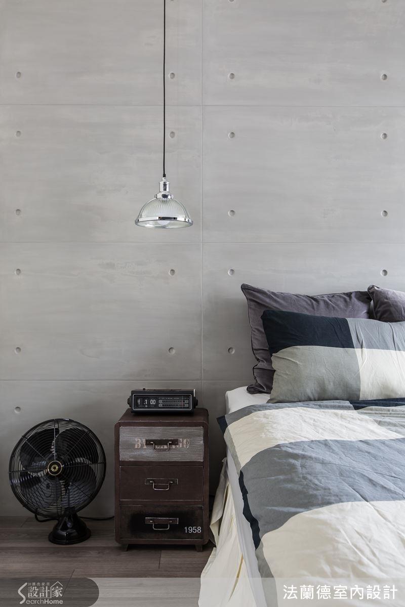 金屬吊燈在清水模質感牆面與老件床頭櫃的襯托下,融合復古與現代性格。