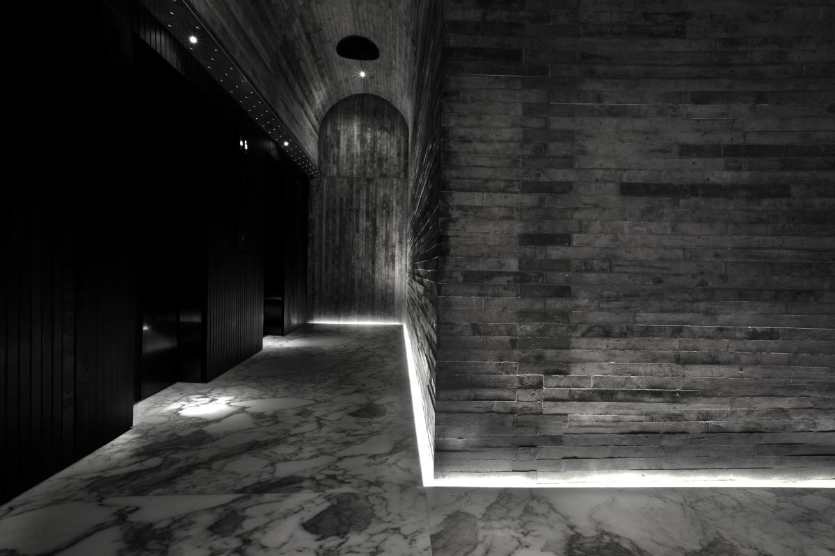 在接待大堂裡,白色大理石蜿蜒的天然紋路,與隔斷牆身投射出的光影相間,交織出躍動淋漓的構圖。而在入口走道的玻璃纖維強化水泥牆體,其錯綜的接合與細密的輪廓在地面泛出的光線映照下昭然可見。