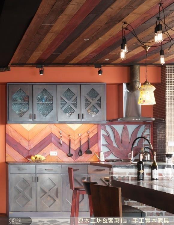 鄉村混工業風的個性廚房,把木素材做了三種型態的呈現。木質流理檯鑲嵌花磚,好清潔又耐熱;流理檯中段的部分,則做了 V 型木質的漸層拼接以及在玻璃下植入藝術感的木質雕花,整體木素材的使用對比深色的廚房,把溫暖活潑的亮度表現出來。