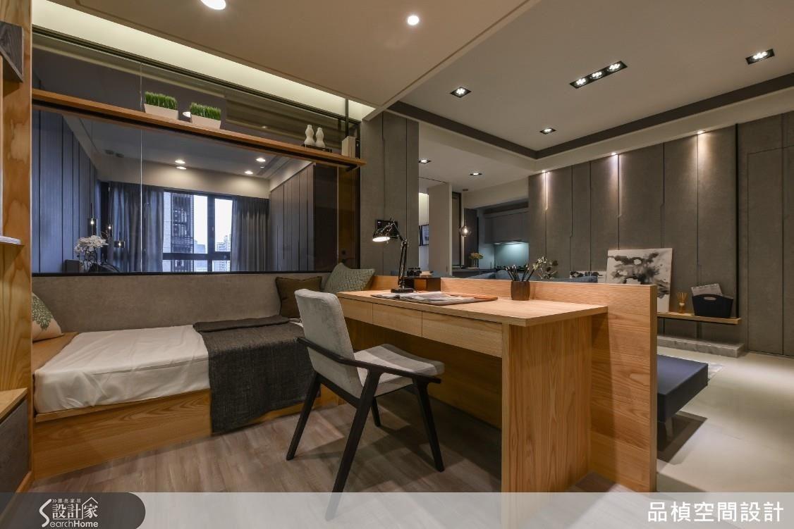 矮沙發牆後是一體兩用的書房書桌,主臥與書房以框窗灰玻建構透光性隔間牆。