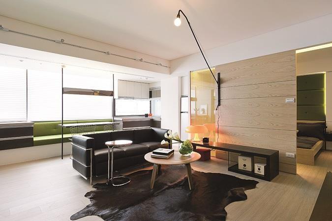 圖2_讓出部份空間給主臥,客廳仍規劃於入門處,以三人沙發做為隔間,並以大型壁燈取代吊燈,連結開放式餐廳,雖是狹長不規則格局,但因為側邊採光充足,且空間又開放,放大了小宅的空間感。 圖片提供_奇逸空間設計
