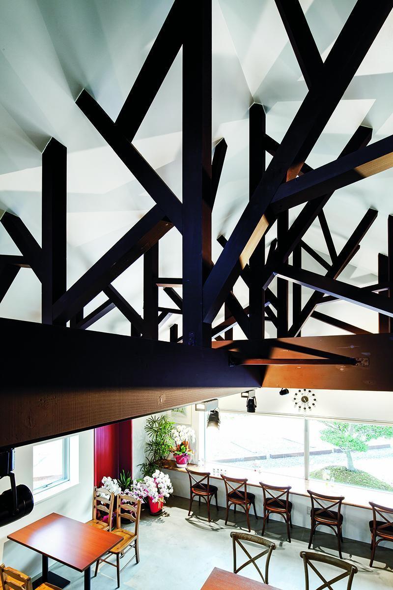 室內用餐區沿著90°牆面配置,目的是盡可能讓每個位置都能欣賞到窗外景色;室內仍以花木為概念設計,坪數雖然不大,但傳統木屋的尖屋頂帶來挑高的空間感,屋頂以桁架結構加強支撐,特別設計成樹枝狀的造型,牆面也大膽以對比紅綠2色塗布,因此觀賞視線無論從裡到外,或者從外到裡皆有如畫作般迷人。