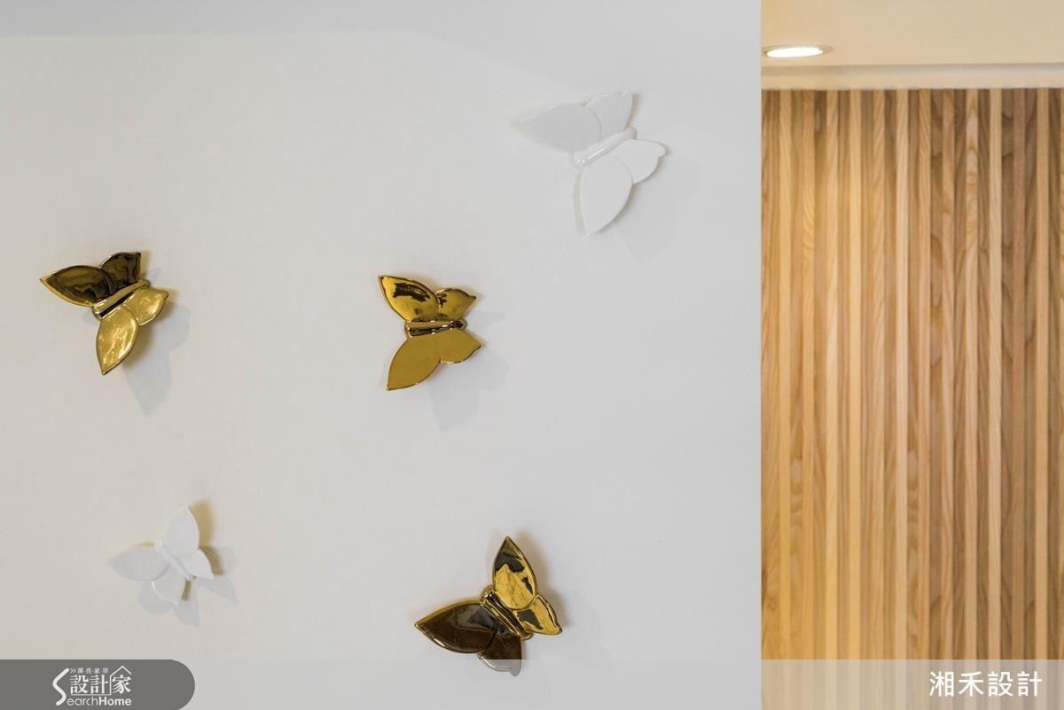 客廳的白色立面上,陶藝品蝴蝶既是與女屋主優雅氣質相符的裝飾品,也是櫃體的把手;金色的質感與木作線條牆面互相呼應,這些巧思串起空間中豐富色彩與質感的整體性。