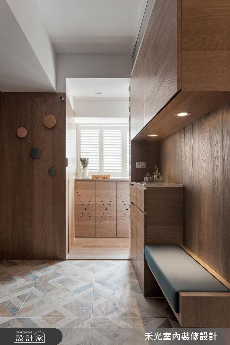 玄關地面鋪設精美花磚,與公領域的木地板明確區隔,端景櫃兩邊皆有動線可進入客廳。