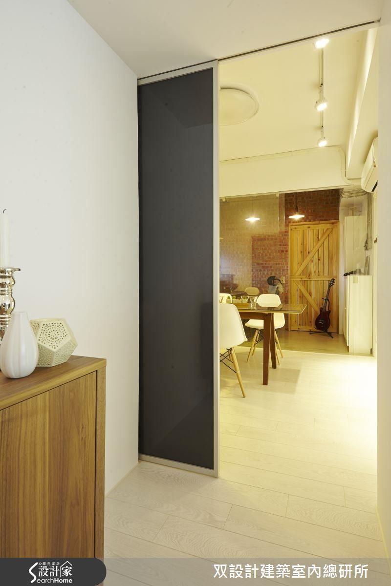 從客廳還須走到廚房還須經過一段走道,設計師以黑色烤漆玻璃搭配金屬邊框打造活動拉門。