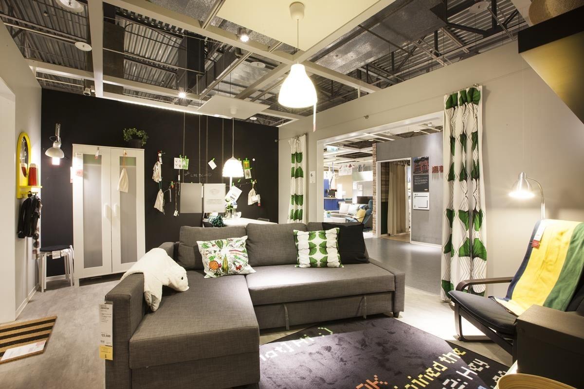 少預算的新手夫妻,選擇以黑灰色的 L 型沙發床呈現居家質感,沙發床擺在客廳正中間,搭配綠色系家飾與窗簾,展現年輕不受拘束的個性。